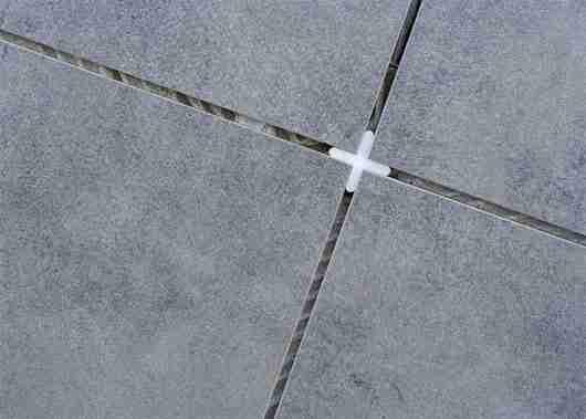 Использование крестика для шва при укладке плитки.
