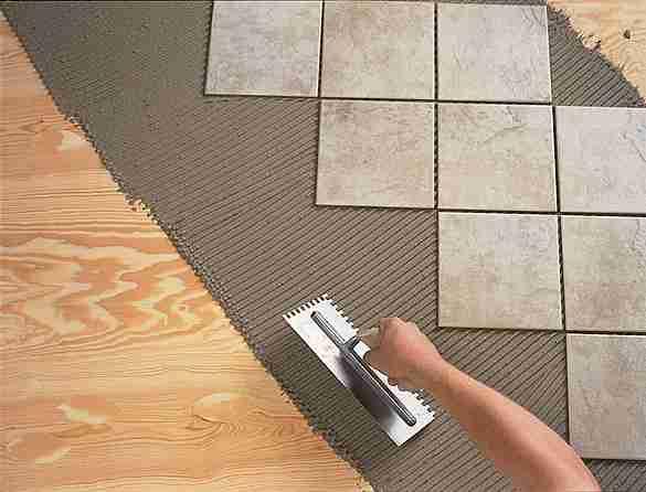 На фото – процесс кладки плитки на фанерное основание.