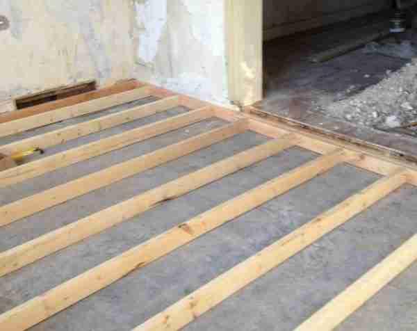 На фото – вариант бетонного пола с установленными лагами для фанеры